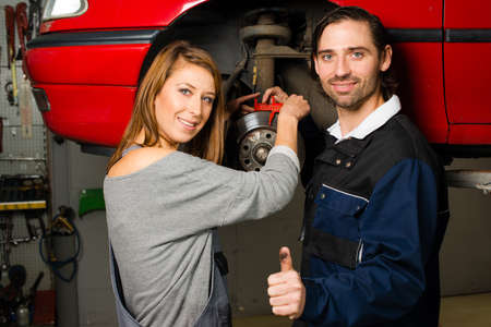 female clothing: Women in male-dominated professions: Auto mechanic is happy with the success of a female trainee during maintenance of the brake disc of a car in a garage. Concept for the fact that more and more women participate in jobs previously typical for men. Stock Photo
