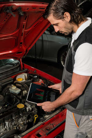 faked: Close-up of a car mechanic using digital tablet in a garage, the tablet displaying (faked) diagnosis data