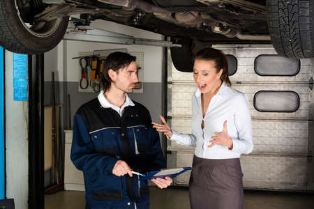 apparently: Car mechanic with attractive but angry female customer going through maintenance checklist in garage - apparently the efforts are overpriced since the woman is screaming at the mechanic. Stock Photo