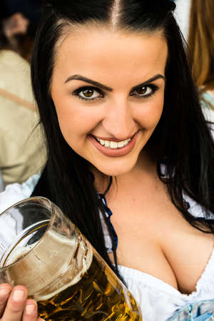 prost: Girl in traditional Dirndl dress, Russian touch but could also be Greek, is drinking beer and having fun at the Oktoberfest Stock Photo