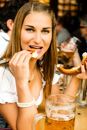 prost: Girl in traditional Dirndl dress is drinking beer and eating a Bretzel while having fun at the Oktoberfest