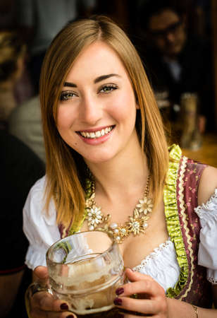 prost: Girl in traditional Dirndl dress is drinking beer while having fun at the Oktoberfest
