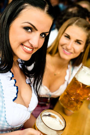 prost: Girls in traditional Dirndl dress, one Russian touch but could also be Greek, one Caucasian are drinking beer and having fun at the Oktoberfest