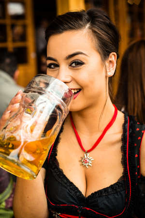 prost: Girl in traditional Dirndl dress, interesting Asian and German multi-racial, is drinking beer and having fun at the Oktoberfest Stock Photo