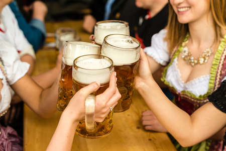 Bavarian girls in traditional Dirndl dresses are drinking beer and having fun at the Oktoberfest