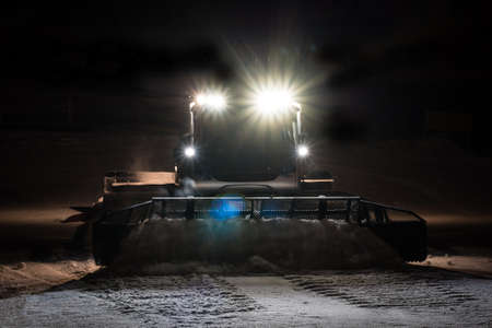 snow grooming machine: Snowcat preparing a slope at night in high mountains at skiing resort