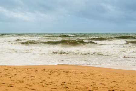 high day: Sand beach with waves and gray-blue sky on a windy day in Albufeira, Portugal