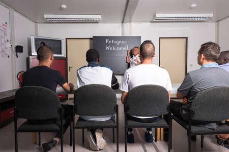 Sprachtraining für Flüchtlinge in einem deutschen Lager: Eine weibliche Freiwillige aus Deutschland unterrichtet junge afrikanische (Gambia) und Arabisch (Algerien und Tunesien) Männer die deutsche Sprache in einem Flüchtlingslager schnell Unterkunftscontainer errichtet werden. Über 1 Million Flüchtlinge Standard-Bild - 58965077