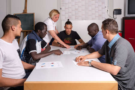 Language training for refugees in a German camp: A female German volunteer is teaching young African (Gambia) and Arabic (Algeria and Tunesia) men the German language in a refugee camp quickly errected using accomodation containers. Over 1 million refugee