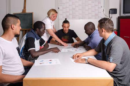 Sprachtraining für Flüchtlinge in einem deutschen Lager: Eine weibliche Freiwillige aus Deutschland unterrichtet junge afrikanische (Gambia) und Arabisch (Algerien und Tunesien) Männer die deutsche Sprache in einem Flüchtlingslager schnell Unterkunftscontainer errichtet werden. Über 1 Million Flüchtlinge Standard-Bild - 58964609