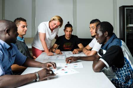 La enseñanza de idiomas para los refugiados en un campo alemán: Un voluntario alemán hembra está enseñando a los hombres jóvenes la lengua alemana en un campo de refugiados errected rápidamente usando recipientes de alojamientos Africana (Gambia) y árabe (Argelia y Túnez). Más de 1 millón de refugiados Foto de archivo - 58964485