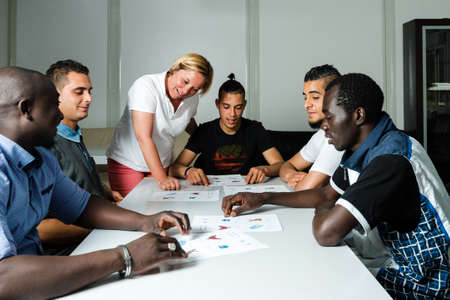 Language training for refugees in a German camp: A female German volunteer is teaching young African (Gambia) and Arabic (Algeria and Tunesia) men the German language in a refugee camp quickly errected using accomodation containers. Over 1 million refugee 版權商用圖片 - 58964485