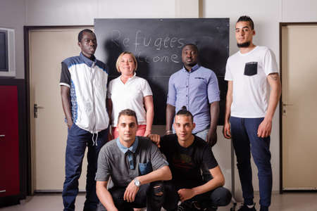 Refugees Welcome: A female German volunteer is proudly posing with young African (Gambia) and Arabic (Algeria and Tunesia) men she is teaching the German language in a refugee camp quickly errected using accomodation containers. Over 1 million refugees ar