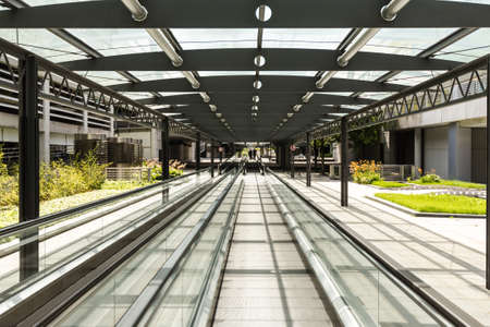 walkway: Modern business architeture: Car parking area with moving walkway and unidentified people in the distance Stock Photo