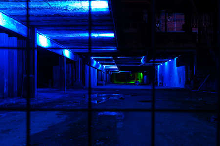 empty warehouse: Strange and dark empty older warehouse  commercial space lit in blue at night