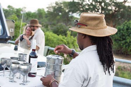 guia de turismo: Parque Nacional Kruger, Sudáfrica - 27 de noviembre 2016: Un guía turístico se prepara bebidas y aperitivos sundowner en la parte delantera de su vehículo 4x4 con una pareja disfrutando de las fotos que se han tomado hasta ahora en el fondo.