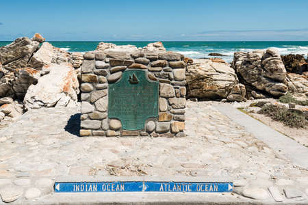 The plate of Cape Agulhas, at the southern edge of the village of LAgulhas, in Agulhas National Park, the southernmost tip of Africa where Atlantic and Indian Oceans meet