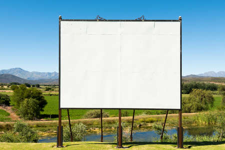 desired: Big blank billboard in a nice scenery along the Garden Route of South Africa. The billboard is hand made, you can see the various boards and screws that could still shine through the image you place on top or of course can be completely hidden as desired. Stock Photo