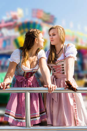 Attractive young women at German funfair Oktoberfest with traditional dirndl dresses