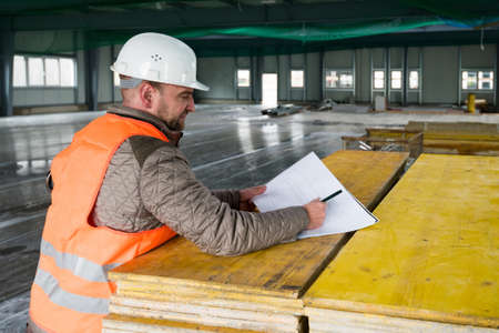 Construction supervisor with plan on site