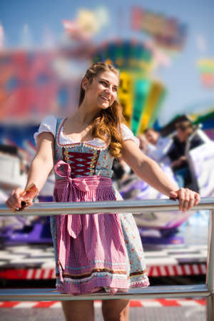 Attractive young woman at German funfair Oktoberfest with traditional dirndl dress