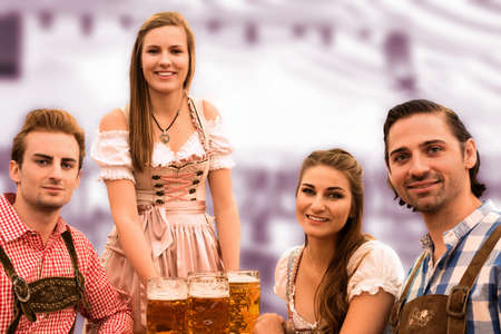 career fair: Waitress delivers beers in tent with happy visitors in a beer tent at Munich Oktoberfest