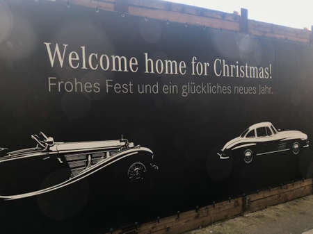 Stuttgart, Germany - December 09, 2017: Merdedes-Benz Christmas Greetings: The car manufacturer is greeting visitors to the Stuttgart Main Station with a huge Christmas banner showing two classic cars.