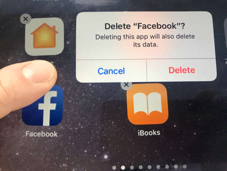 Macro image of a finger about to delete the Facebook app from an iPad screen - might be due to data privacy issues, Facebook is currently facing