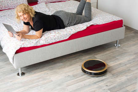 Vacuum cleaning robot with relaxed woman reading in the background