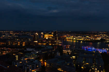 Aerial view of Hamburg, Germany in the evening with fireworks next to the new Elbphilharmony (Elphi) and illuminated boats