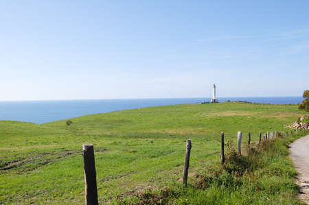 cantabrian: Beautiful lighthouse with the Cantabrian sea behind and a green field in the foreground. Located in Lastres, Asturias, North Spain. Stock Photo