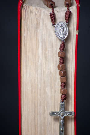 A Bible and a wooden rosary. Black background photo