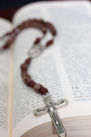 Opened Bible with a wooden rosary photo