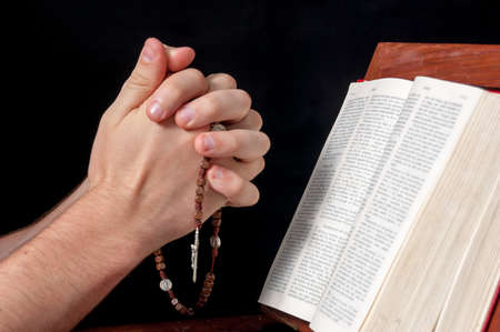 Hands praying and holding a rosary. Bible on a lectern. Black background photo