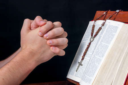 Hands praying in front of a Bible and a rosary photo