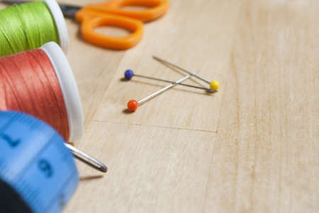 Close up of sewing items, cut off at left side of frame with three colourful pins in centre of frame.  These are placed on a birch wood table, which provides some copy space in areas containing no items. Stock Photo - 5830384