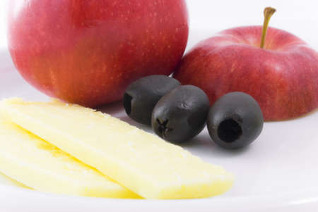 elevenses: Red apple, black olives and cheddar cheese on white china plate.