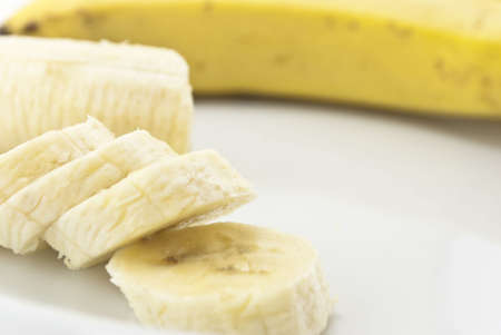 unpeeled: Close-up of bananas in various states:  Peeled and sliced, remaining portion, and whole, unpeeled. Composition set on a white china plate. Stock Photo