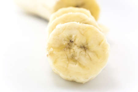 peeled banana: Close-up shot of banana slices in foreground, with remainder of peeled banana in soft focus in the background.  White background.