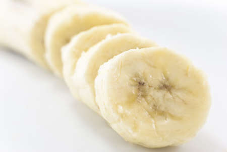 Close-up of sliced banana seated diagonally across frame with white background on either side.  Main portion in soft focus in the background. photo