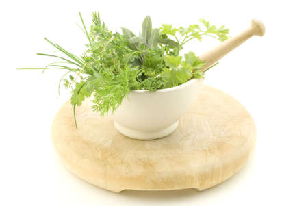 herbalist: A selection of herbs inside a cream mortar with pestle, standing on light wood chopping board which shows signs of wear.  Isolated against white background. Stock Photo