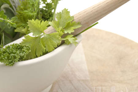naturopath: Closeup of a selection of herbs in a cream coloured mortar with pestle on worn wooden chopping board.  Subject cuts off at left edge of frame.  Isolated against white background. Stock Photo