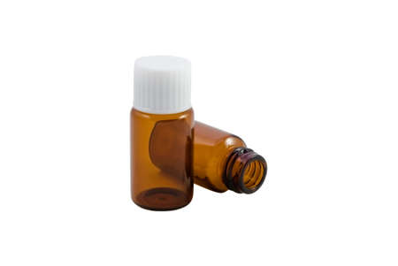 homoeopathic: Two amber glass pill bottles, as used in homeopathy.  One upright with lid, one lying open on its side.  Isolated with white background. Stock Photo