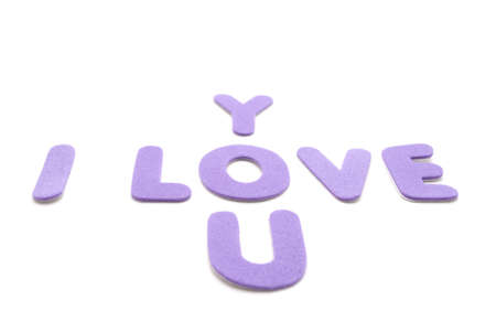 The words I love you spelled out in mauve or purple foam lettering against a white background. photo