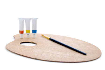 Three tubes of paint (primary colours) and a blackgold paintbrush, standing on a wooden artists palette, isolated against a white background.  Shadows visible.  Whole composition in frame. photo
