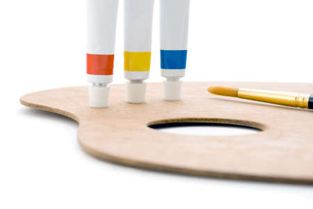 Three tubes of paint (primary colours) standing on edge of wooden palette with thumb hole and paintbrush tip visible.  Closeup shot, cropped in camera so only leftmost portion of palette is visible.  Isolated against white background. photo