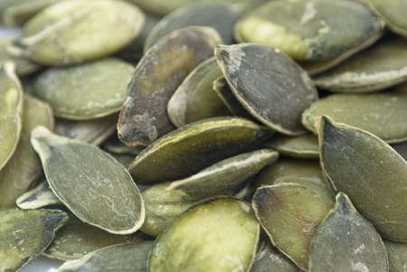 Close-up shot of numerous organic pumpkin seeds in their raw state.
