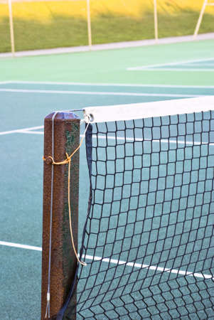 municipal court: Tennis court net attached to rusting metal post with yellow and grey ropes.  Tennis court of green tarmac is visible.  Out of focus wire fence and shadowed grassy hill in background.  Winter daylight.