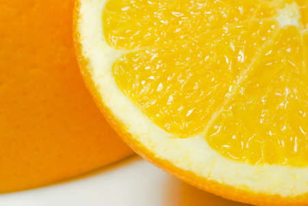 upturned: Close up (macro) of one slice of orange (quarter visible in foreground) leaning against upturned orange half, on white china surface with visible shadows. Stock Photo