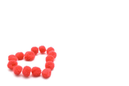 wooly: A heart shape made up from assembled red fluffy pompom balls, seated at lower left of image.  White background with copy space.